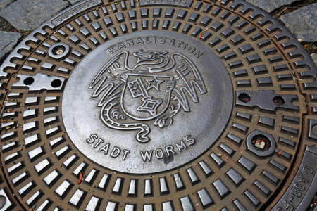 Worms, Germany - 06 29 2020: Manhole cover with coat of arms of Worms