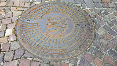Seligenstadt, Germany - 07 12 2020: Manhole cover with the coat of arms of Seligenstadt Editorial