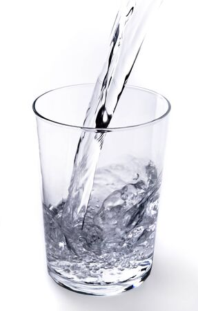 Water filling a glass on white background Zdjęcie Seryjne