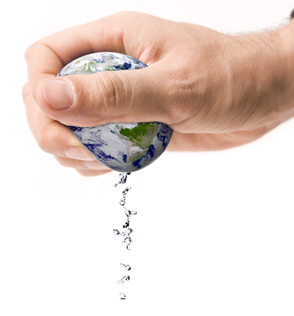 Hand squeezing earth with water drops isolated on white Foto de archivo