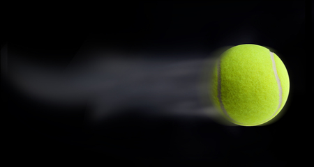Tennis ball fast moving on black background