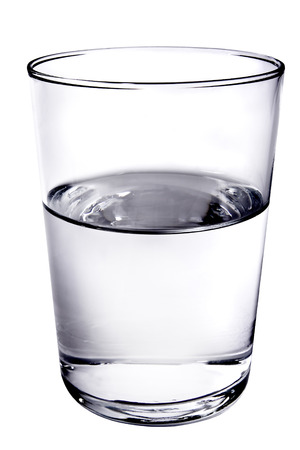 Glass half filled with water on white background