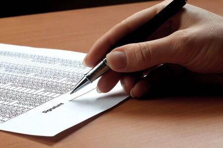signing authority: hand with black pen sign the document Stock Photo