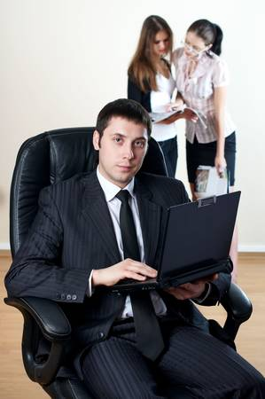 businessman with laptop sit in an armchair with collgues on backside Stock Photo - 6038091