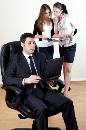 businessman with laptop sit in an armchair with collgues on backside Stock Photo - 6104397