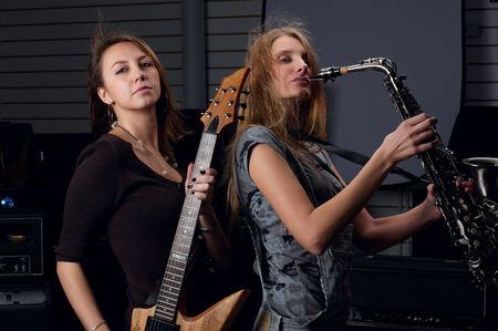 two young female play on guitar and saxophone photo