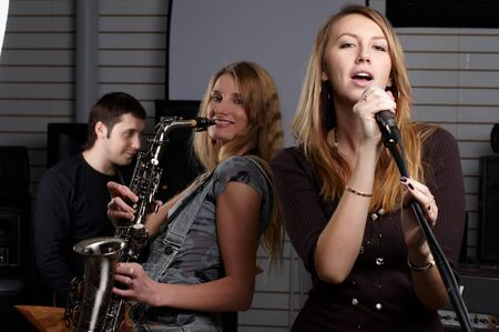 two young females sign the song and play on saxophone photo