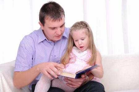 The little girl is sitting on the lap of his father, and reads with him a book  photo