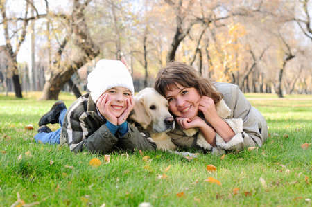 Mother and son together having fun in the autumn park playing with a golden retriever  photo