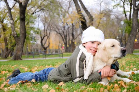 Boy playing in autumn park with a golden retriever  photo