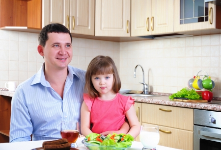 Father and his young daughter eat breakfast together in his kitchen  photo