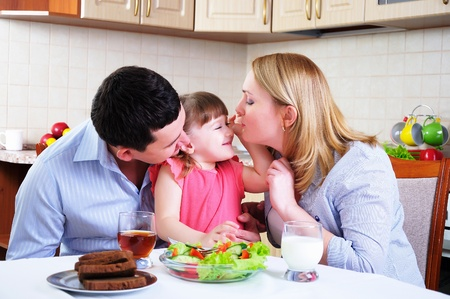 Dad, Mom and their little daughter lunching together in his kitchen  photo