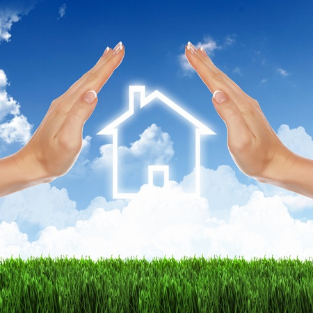 loans: Human hand against blue sky background and house Stock Photo