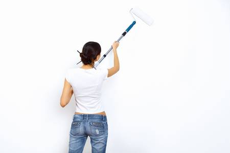 Young woman with paint brushes doing renovation and white wall photo