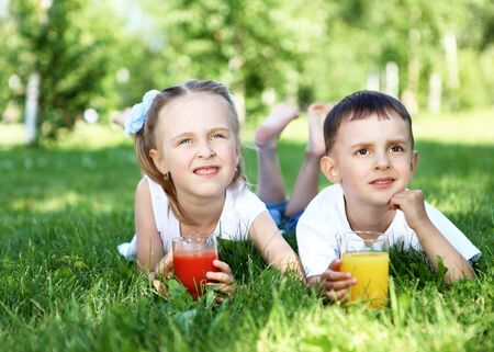 Little brother and sister lying on the grass together in summer park photo