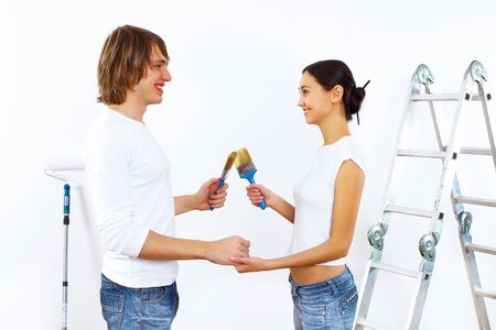 Young couple with paint brushes doing renovation together Stock Photo - 11794171