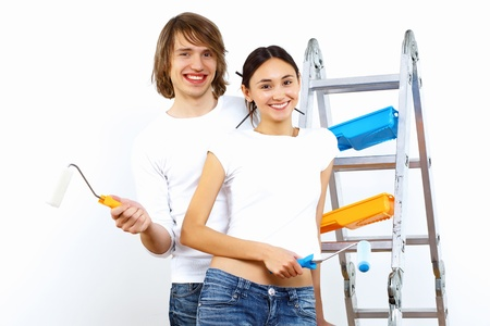 Young couple with paint brushes doing renovation together Stock Photo - 11794170