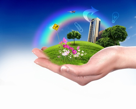 global village: Collage with a human hand holding a green landscape Stock Photo