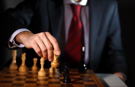 planificacion estrategica: Imagen de un hombre de negocios en traje oscuro jugando al ajedrez