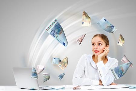 letra de cambio: Joven empresaria en la oficina con el dinero de los billetes a su alrededor Foto de archivo