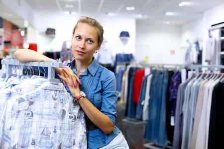 kledingwinkel: Jonge vrouw in een winkel kopen van kleding Stockfoto