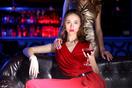 Young woman in evening dress in night club with a drink Stock Photo - 11793899