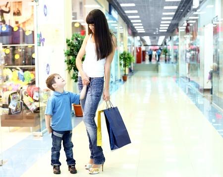ni�os de compras: Joven madre con bolsas de compras que realizan las compras