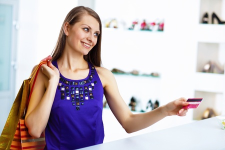 Young pretty woman doing shopping with credit card photo