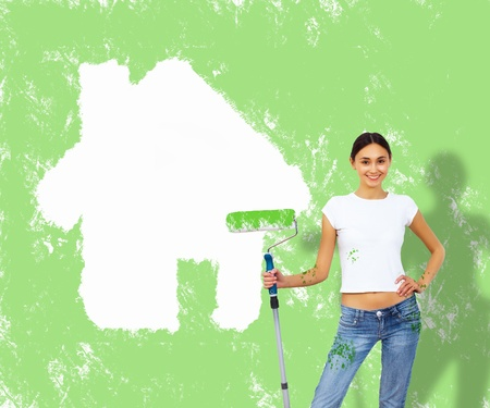 aucasian: Young woman with paint brush and white wall with house on it Stock Photo
