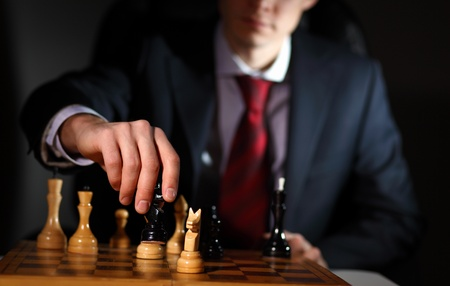 battle plan: Image of a businessman in dark suit playing chess
