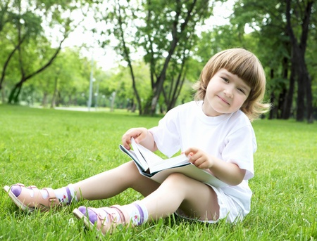 Portrait of little girl reading a book in the summer park photo