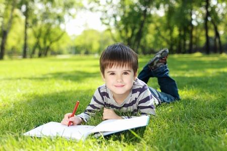 Portrait d'un gar�on couch� sur l'herbe avec un livre dans le parc