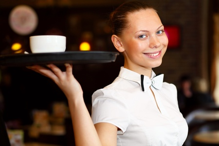 Portrait of young waitress in white blouse holding a tray photo