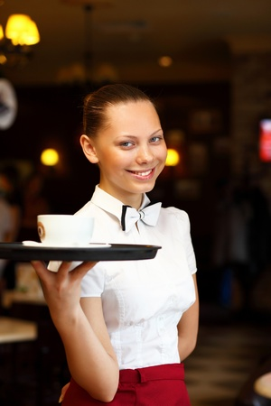catering service: Portrait of young waitress in white blouse holding a tray