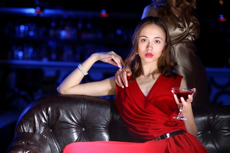 Young woman in evening dress in night club with a drink Stock Photo - 11846883