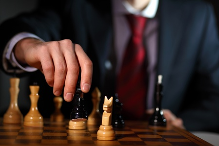 checkmate: Image of a businessman in dark suit playing chess