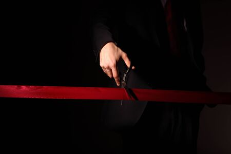 launch: Hand of a businessman with scissors cuting a red ribbon