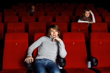 Young man sitting in cinema and watching movie photo