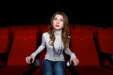 alone in crowd: Young girl sitting in cinema and watching movie