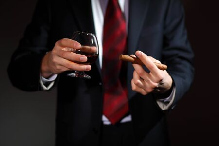 Businessman holding a glass of cognac and cigar photo
