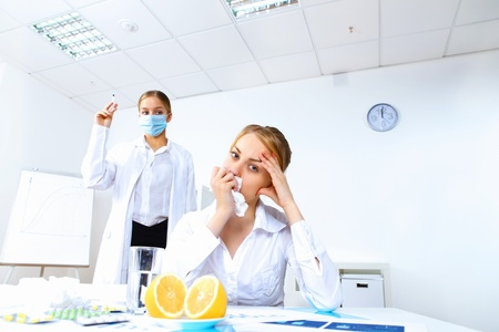 Young nurse with syringe doing vaccination in office photo