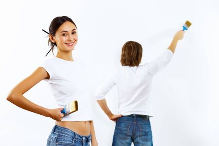 Young couple with paint brushes doing renovation together photo