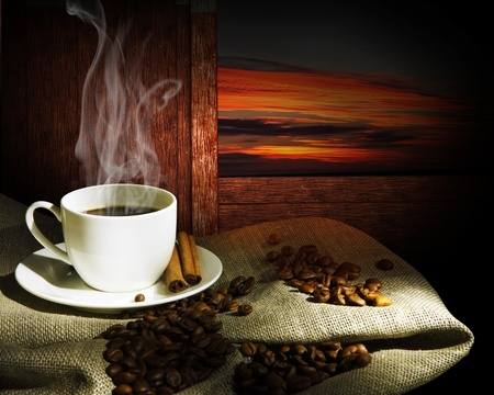 Steaming cup of coffee, cinnamon sticks and a few coffee beans. still life photo