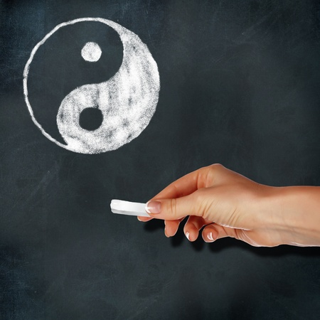 School blackboard and hand with chalk drawing yin-yang symbol Stock Photo - 11986802