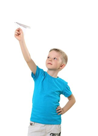 little boy in blue T-shirt with paper plane in studio photo