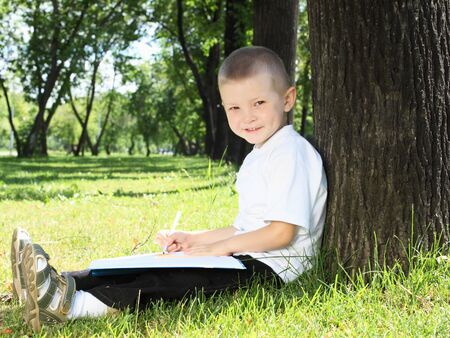 Portrait of a boy sitting with a book in the park photo