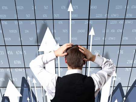 Young businessman thinking and analyzing financial graphs Stock Photo - 11987082