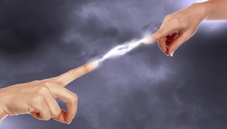 electric charge: Two human hands in contact with bright flash