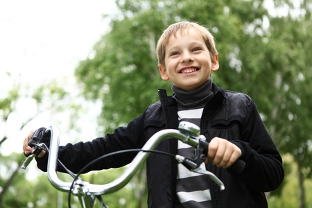 Happy smiling boy on a bicycle in the green park photo