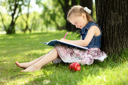 Portrait of a little girl sitting and reading on the grass in the park photo